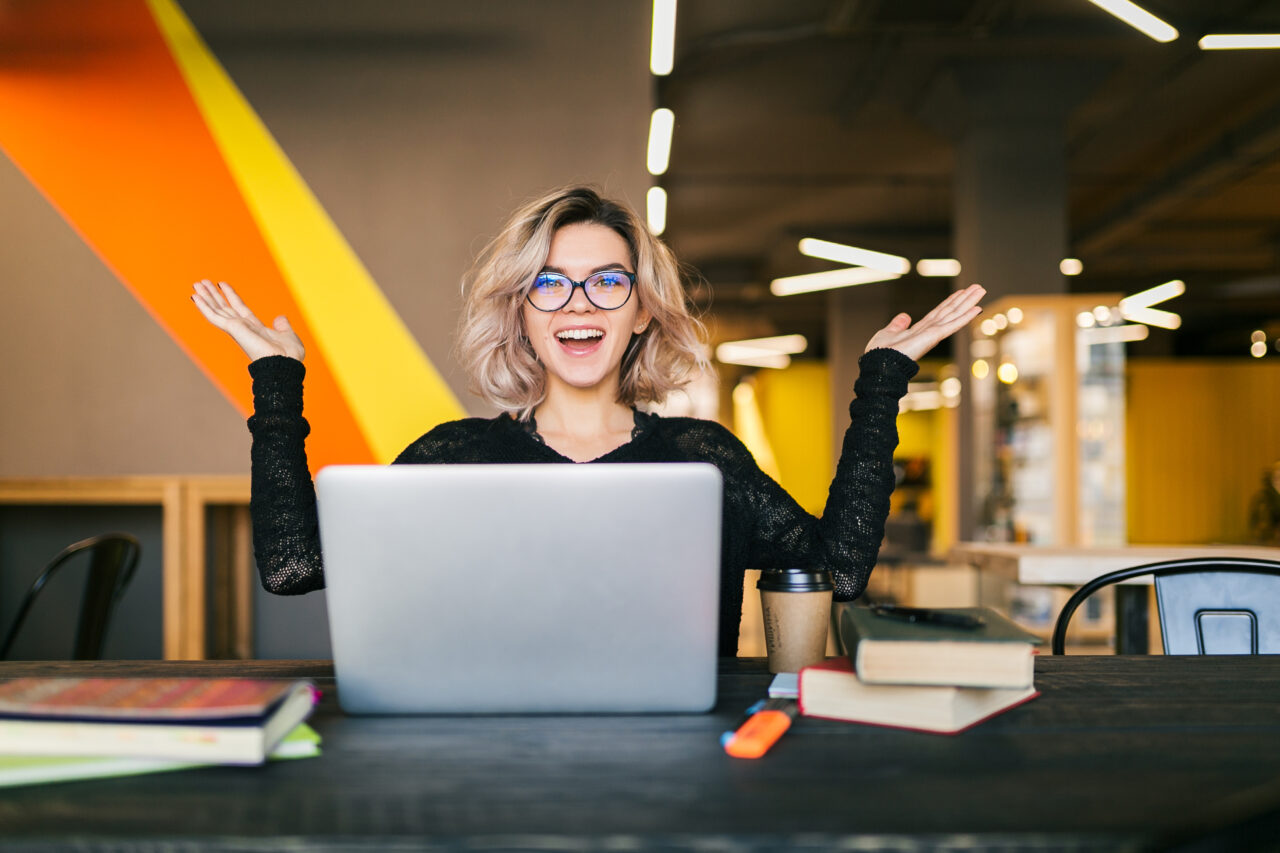 https://ekaenlinea.com/wp-content/uploads/2021/10/funny-happy-excited-young-pretty-woman-sitting-table-black-shirt-working-laptop-co-working-office-wearing-glasses-1280x853.jpg